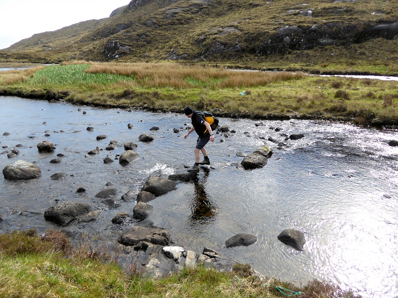 Mike crossing the stepping stones as bridge gone! Photo by Mike Goodyer